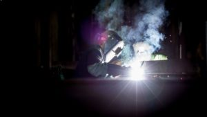 Welders working in the a dimly lit space
