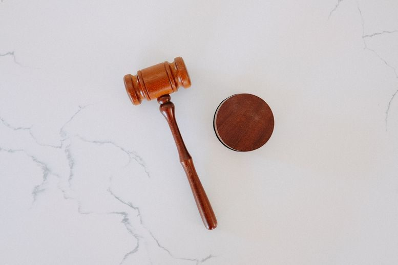 A gavel on a white marble tabletop.