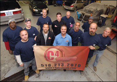 All On Board: Cole's Collision techs are paid a flat rate, which John Cole, center in the blue shirt, says motivates them to work hard—and drive down cycle times.  Photo by Liz Lajeunesse