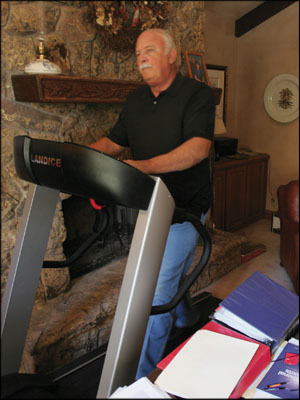 HOME AT WORK: Gene Crozat working out on the treadmill in his office. Photo by Kent Proter