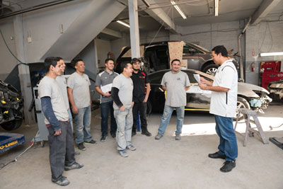 On the Same Page: At the beginning of each day, owner Luis Gonzalez meets with his LG Auto Body team to map out the shop's upcoming schedule.