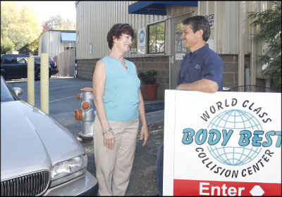 GIVING BACK: Dino Di Giulio, here with vehicle recipient Kathleen St. John, says Wheels to Prosper allows him to give back to the community that makes his shop successful. Photo by Rick Bolen
