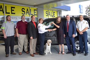 Fire Investigator Roseanne Moreland and K9  Gracie of the Ocala Fire Department in Florida receives keys to a Recycled Rides from State Farm and Jenkins Collision Center in Ocala, Fla. Image courtesy of NABC.