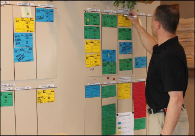 PRECISION SCHEDULING: Lobsiger and his staff developed this scheduling board to give a clear, color-coded visual of the shop's in-process jobs. Photo courtesy Loren's Body Shop