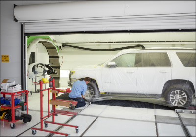 SMOOTH TRANSITION: Vehicles at Body Shop Express are masked and put on a rail system that allows the vehicle to slide easily in and out of the booth, which is equipped with a full-arch dryer (left).