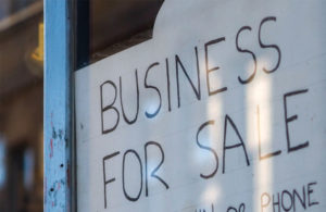 """A sign in a window that says """"Business For Sale."""""""